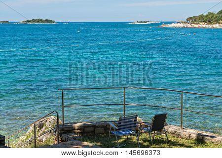 Rocky beach, two chairs and bue sea in Istria, Croatian coast