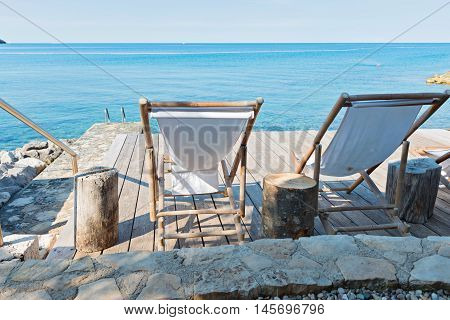 Wooden floor with chaise-longues and bue sea in Istria, Croatian coast