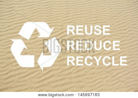 Recycle logo on sand with text reuse reduce recycle