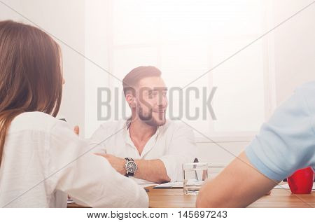 Business meeting. Young happy smiling businessman candid portrait at modern office, team corporate discussion at workplace. Communication with partners for startup, high-key candid image in sunlight