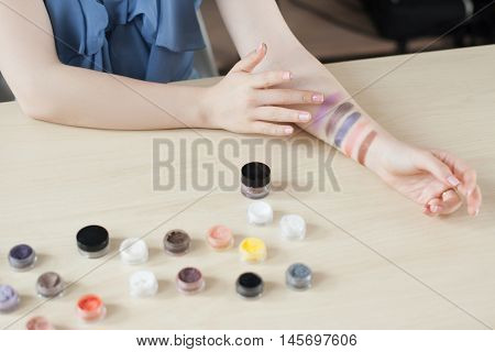 Make up artist testing eyeshadow colors. Woman stylist trying cosmetics color on her hand. Professional coloring, visagiste, swatch concept