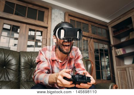 Excited man playing video game in vr glasses with joystick. 3d virtual headset impressed male adult. Modern technology, innovation, cyberspace, entertainment, gaming concept