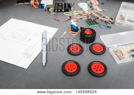 Components and scheme of constructing car at home. Engineer workplace with wiring diagram and wheels for toy truck, diy modeling, modern technologies, hobby