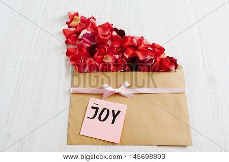 Floral present with rose petals and joy text, flat lay. Beautiful greeting composition made from red flower bloom and brown kraft envelope on white wooden background