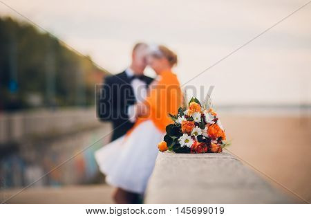 Beautiful wedding flower bouquet with orange roses and orange camomile.. Wedding decor, idea, background. Bride and Bridesmaid on background