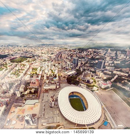 KIEV, UKRAINE - JULY 10, 2016: Aerial view of the Olympic Stadium and Kiev city. Ukraine. The field for the football game. The largest stadium of city from helicopter. Outdoor.