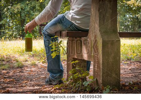 Man Depressed With Beer Bottle Sitting On A Park Bench