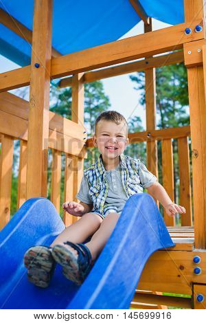 Smiling kid having fun at playground. Child playing outdoors in summer. Boy sitting on children's slide.