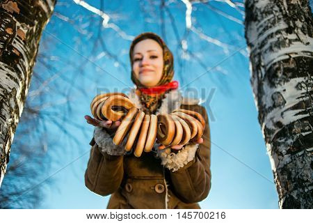 young beautiful woman in national russian suite show bagels at sunny winter day between birches.