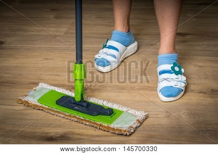 Woman With Mop Mopping Wooden Laminate Floor