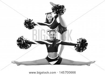 Two professional cheerleaders posing at studio. Side split and vertical split. Isolated over white.Black and white photography