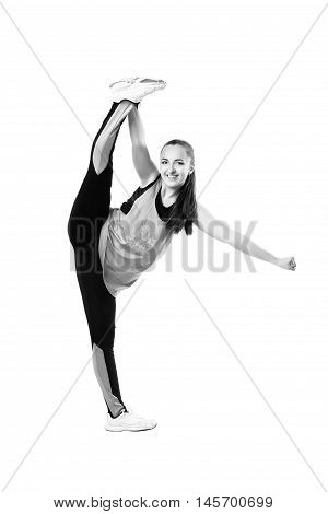 Young professional cheerleader stands in vertical splits. Isolated over white. Black and white photography