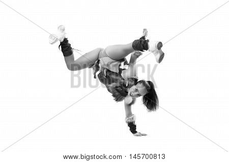 Young professional cheerleader dressed in a warrior costume standing on one hand. Horizontal splits. Black and white photography