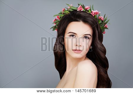 Perfect Woman with Summer Pink Flowers Crown. Brunette Beauty. Long Permed Curly Hair and Fashion Makeup