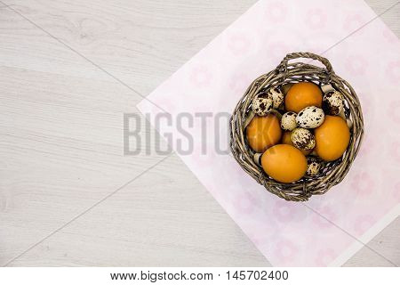 Plate with quail eggs and chicken eggs. Quail eggs in a wooden bowl. place for text. nutrition protein diet. Top view flat lay with copyspace for slogan or text message. colorful background