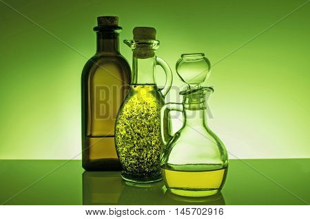 Olive oil in three different glass bottles with reflection on green background