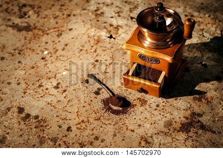 Close up view of ?ld wooden manual grinder and ground coffee on a spoon
