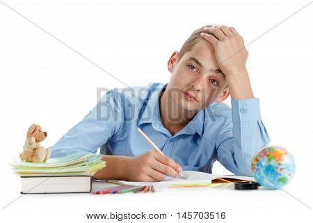 Boy sits thoughtful near desk with school supplies isolated on white background schoolboy ponders lesson learning and homework