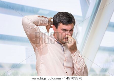 Man With Sweating Under Armpit Pinches Nose With Fingers
