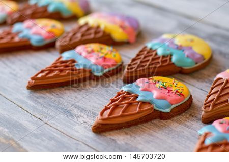 Biscuits on gray wooden surface. Bright-colored desserts. Tasty ice cream cone cookies. Delicious surprise for kids.