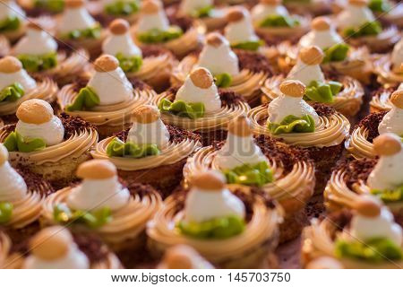 Rows of small decorated cakes. Chocolate crumbs and cream. Appetizing fresh desserts. Sweet treats in cafe.