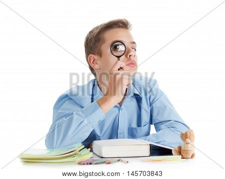 Fun schoolboy sits near the desk with school supplies isolated on white cheerful childhood