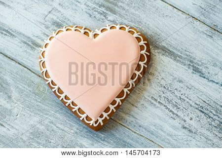 Heart shaped biscuit with icing. Decorated cookie on wooden background. Sweet taste of love. Find your happiness.