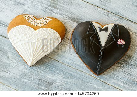 Wedding cookies on gray background. Biscuit shaped as tuxedo. Sweet treats for loving hearts. Best regards to newlyweds.
