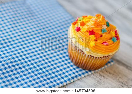 Bright cupcake on napkin. Small dessert with colorful icing. Pastry served at local bistro. Discover beauty of simple things.