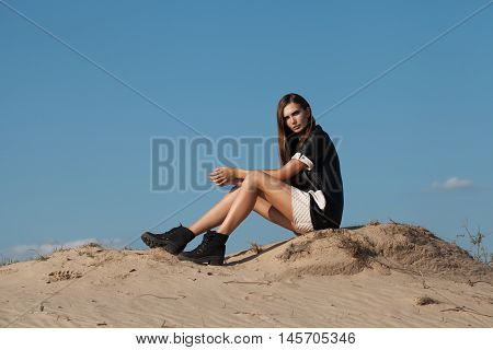 Creative Shot In The Desert. A Beautiful Sexy Girl In A Black Dress. T