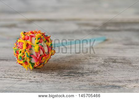 Candy with frosting and sprinkles. Colorful cake pop. Dessert will lift your mood. Be happy and energetic.