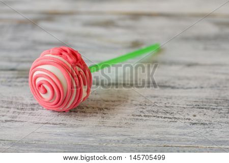 Cake pop with pink frosting. Candy lying on wooden surface. Find recipe of good mood. Sweeten up the day.