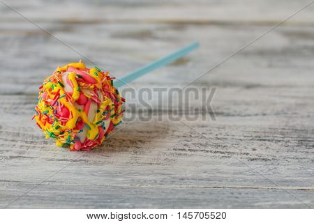 Cake lollipop with sprinkles. Candy on wood background. Sweeten up the life. You'll never forget this taste.