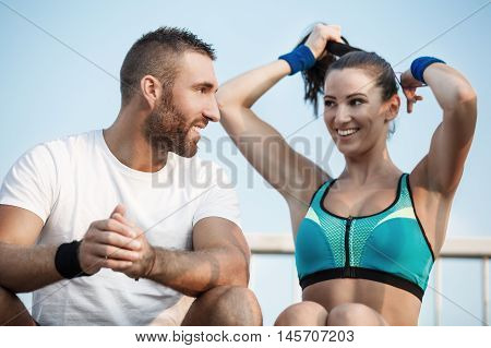 Happy couple releaxing after exercising outdoors. Living healthy lifestyle.