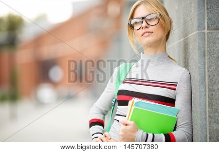 dreamy blonde spectacled near wall of building