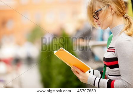 blonde with glasses reading book on street before building