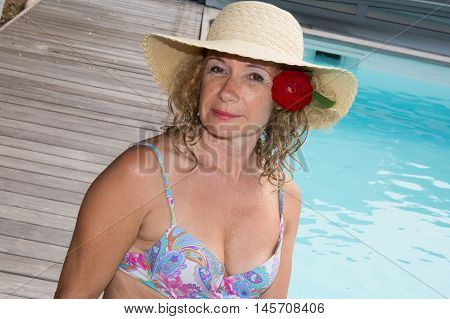 Middle Aged Woman That Is Sitting In Blue Water Of Swimming Pool And Imitate The Hug Gesture.