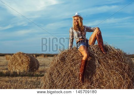 Lovely fashion woman in cow girl country style on hay stack. Beauty romantic girl outdoors against hay stack. Photo of sexy blonde in a field with haystacks