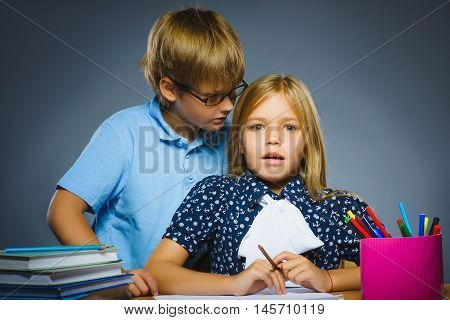 boy whispering in the ear of Teenager or girl on gray background. Communication concept.