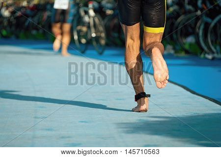 Running triathlete in the transition zone, runner after swimming
