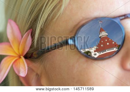 Relaxing Girl Wearing Sunglasses, a Plumeria Flower In Her Hair and Reflection of Hotel Del Coronado In Her Sunglasses.