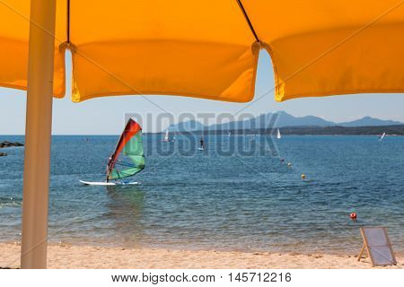 Yellow Beach Umbrella, Windsurfer, Hills And Sea In Background