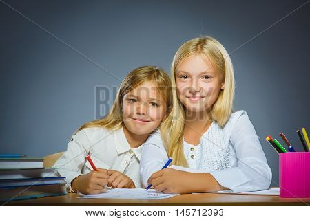 school concept. Closeup portrait successful happy girls drawing pencil on gray background