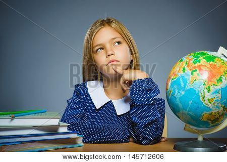 school concept. girl sitting at the desk in the classroom Geography.