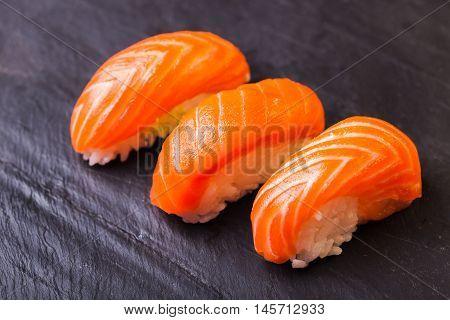 Close-up of Sake sushi with salmon on a black slate background