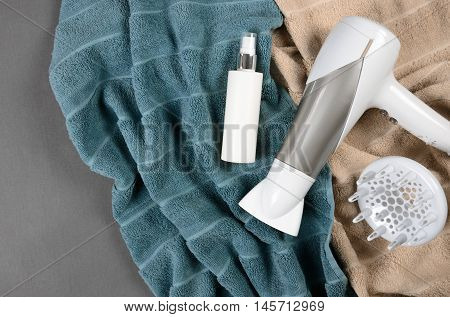 Hairstyling Tools (white Hairdryer, Hairspray) On Beige And Greenish-blue Towels. Top View.