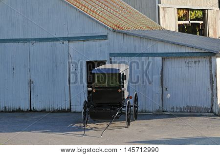 Amish buggy parked in front of Tobacco barn in Lancaster Pennsylvania countryside