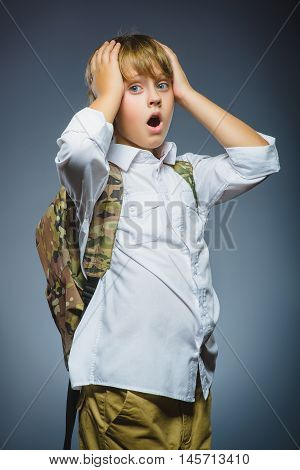 school concept - astonished or doubt expression. boy with knapsack on gray background.