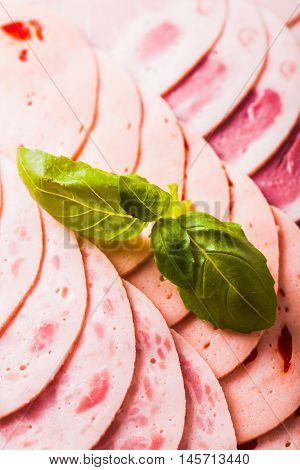 Meat delicatessen plate decorated with basil leaves on a black background