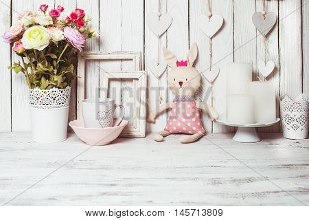 Valentine day gifts such as rose in white vase, white mug, scented candles, empty frames and toy bunny